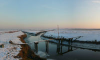 Ebb and Flow on Blue in the snowy wetlands after getting painted with sea-clay and fastened to a bridge